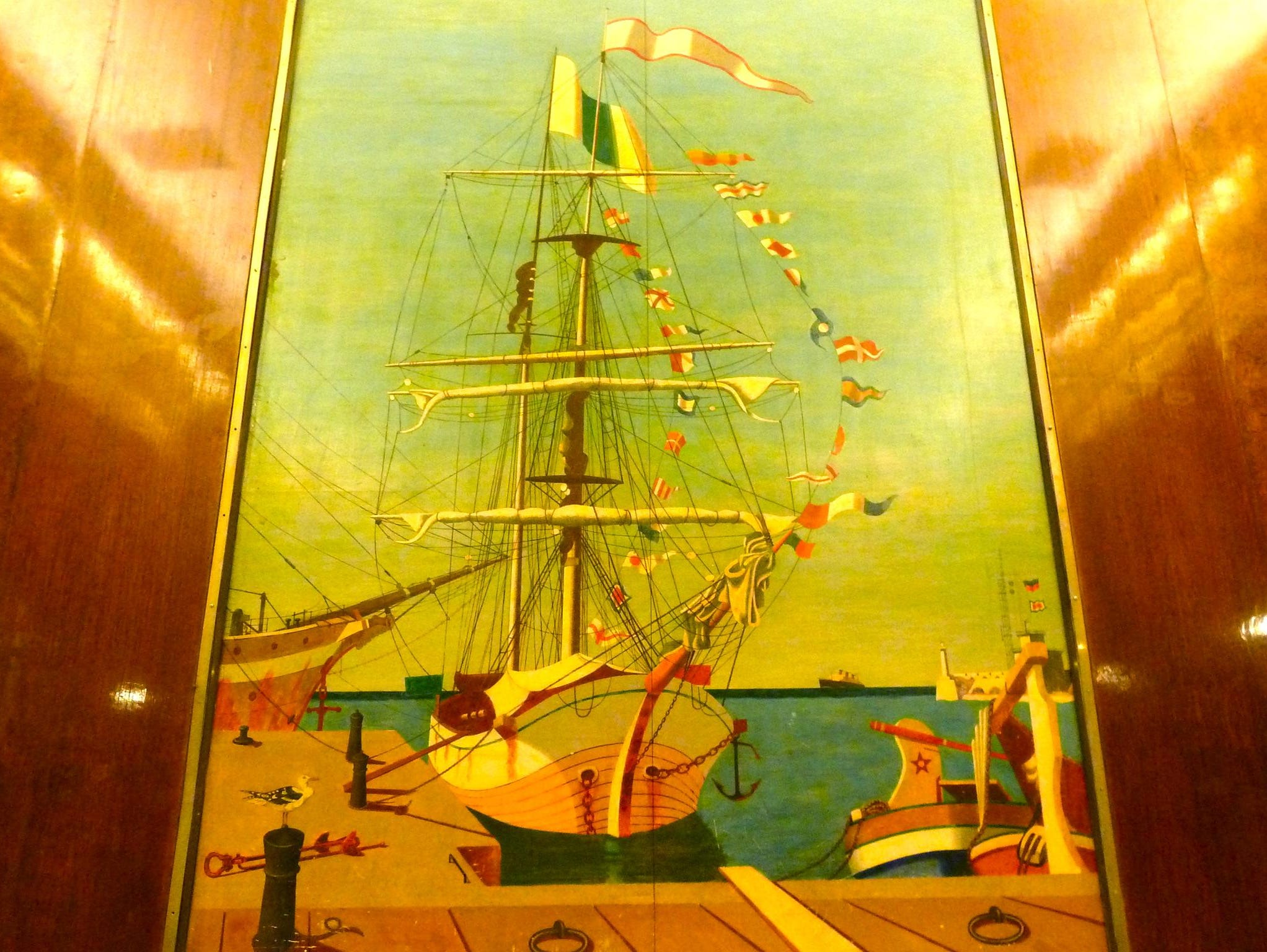 This is a view of the Royal Salon's forward Wadsworth painting. On the horizon, to the right of the sailing ship in the center, is an approaching Queen Mary. Other highlights in the room are the silvered bronze grating and acid-etched glass lighting fixtures.