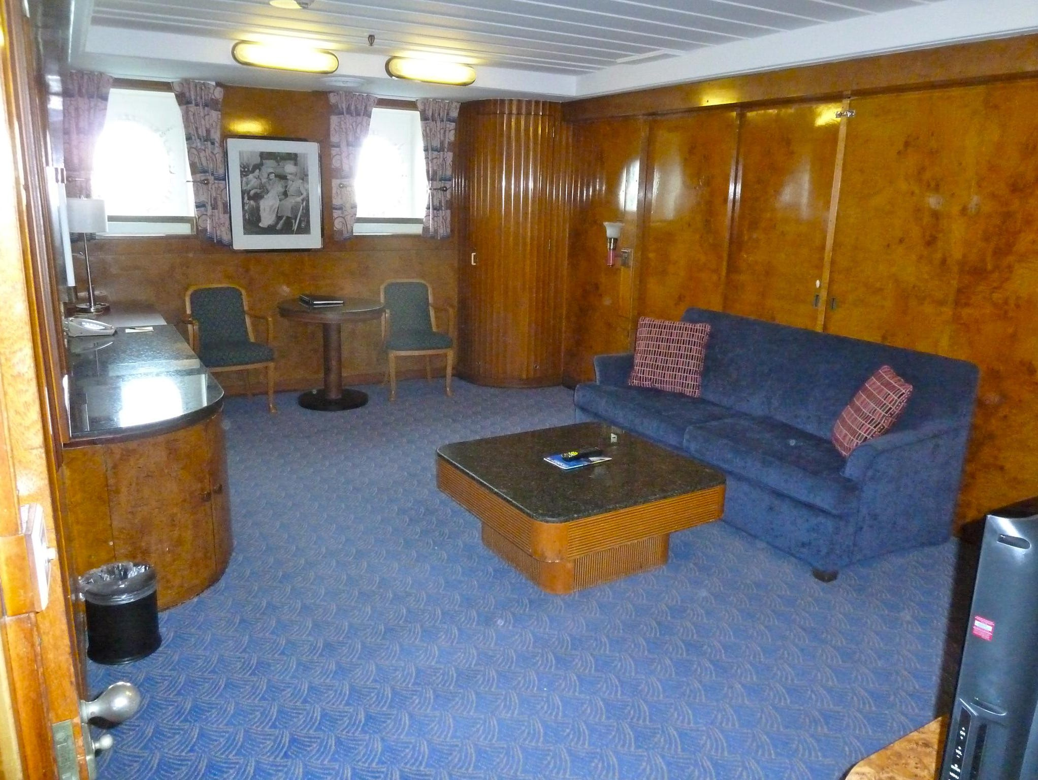 This is the sitting room in the Queen Mary Suite, also equipped with a pair of brass-framed portholes. The black granite table and countertops were fitted in the Long Beach conversion and iPod docks and flat-screen televisions are recent additions.