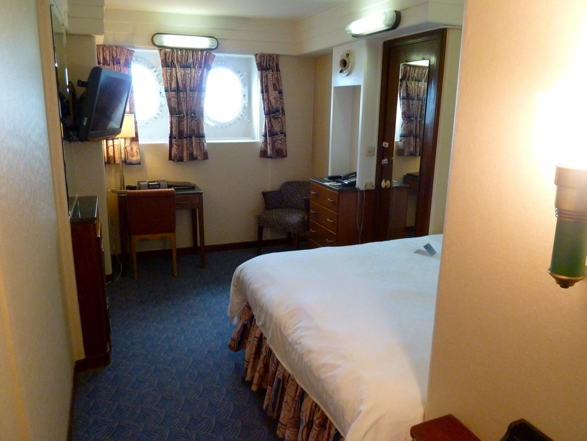 This is a semi-original cabin that has some Cunard-era fittings and furniture but no wood paneling.
