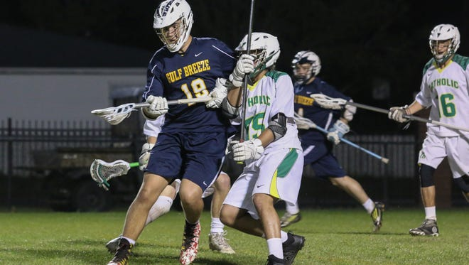 Gulf Breeze's Noah Haas (19) maintains control of the ball as Catholic's Evan Castro (55) hits him Friday night at Catholic High School.