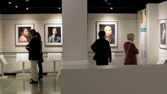 """Visitors to the Hayes Presidential Library and Museums check out the special exhibit """"Bhutanese-Nepali Neighbors: Photographs by Tariq Tarey"""" on display in the lower level of the museum."""