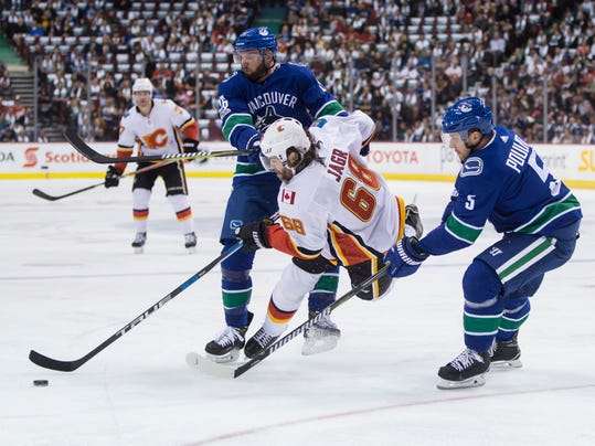 Calgary Flames' Jaromir Jagr, center, of the Czech Republic, is checked to the ice by Vancouver Canucks' Thomas Vanek, back, of Austria, in front of Derrick Pouliot during the first period of an NHL hockey game, Saturday, Oct. 14, 2017 in Vancouver, British Columbia.  (Darryl Dyck/The Canadian Press via AP)