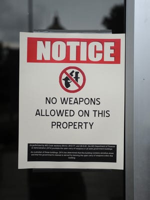 Signs posted outside the Woolfolk State Office Building in Jackson warn that weapons are not allowed on the premises.