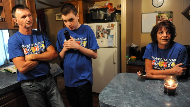 Dhalton Dickerson, 18, paces back and forth from the kitchen to the living room between his parents, Kevin Dickerson and Tammy Moore at his father's South Zanesville home. Dhalton, who was diagnosed with autism at two years old, attends Starlight Academy in Zanesville, to which his parents credit Dhalton's skill development and improved behavior.