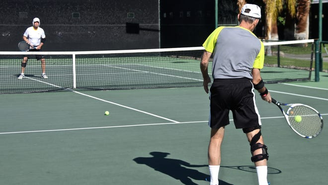 Attendees play tennis at Plaza Racquet Club on Monday, Dec. 7, 2015.