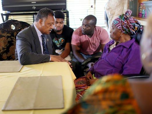Rev. Jesse Jackson (L) speaks with Nowai korkoyah (R),