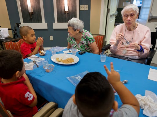 Four-year-old Alejandro Asin, left, visits with Naples residents Mary Caye Markham, center, and Virginia Nagy, right, while celebrating Johnny Appleseed Day with apple pie-in-a-cup at the Beach House Naples Assisted Living & Memory Care in East Naples on Monday, Sept. 26, 2016. Preschool students from The Salvation Army Naples Childcare Center visited residents of the assisted living facility Monday as the first of a series of visits planned to bring the school's young children together with the seniors.