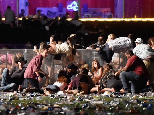 People scramble for shelter at the Route 91 Harvest country music festival after apparent gunfire was heard on Oct. 1 in Las Vegas. A gunman opened fire on a music festival in Las Vegas, leaving at least 59 people dead and 527 injured.