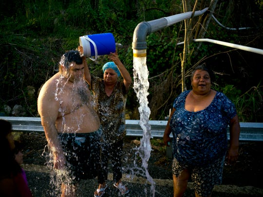 Residents bathe in water piped from a mountain creek in Utuado, Puerto Rico, on Oct. 14, 2017, nearly a month after Hurricane Maria made landfall.