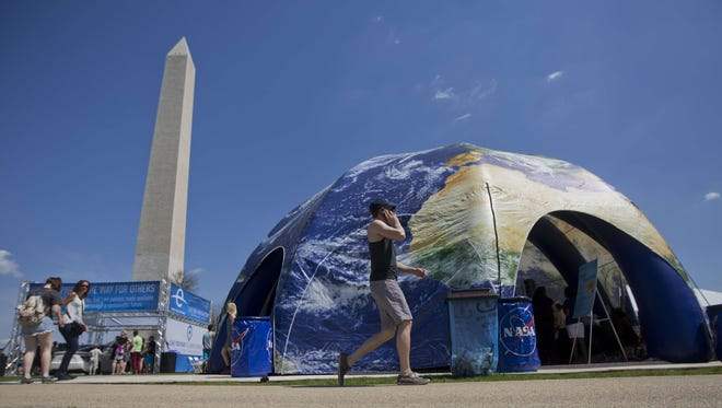 A man walks past a dome with a picture of the Earth during the 2015 Earth Day concert in Washington, D.C., on April 18, 2015.
