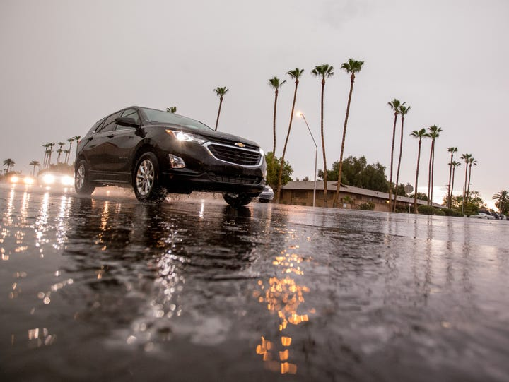 Cars drive past the rain along Rural Road on July 9,