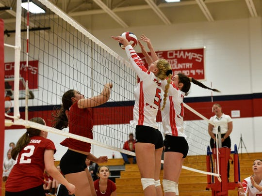 Marathon's Hope Krautkramer attempts to hit over the block of Pacelli's Emily King (5) and Molly Lawlis on Thursday night.