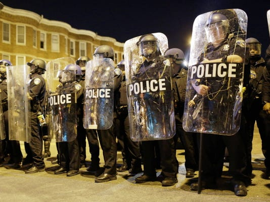 FILE - In this April 28, 2015 file photo, police stand in formation as a curfew approache in Baltimore, a day after unrest that occurred following Freddie Gray's funeral.