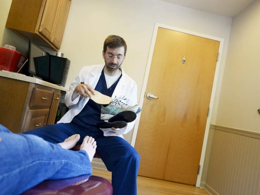 Dr. Jeffrey Kauffman fits Kim Kauffman of Red Lion with custom orthotics recently to treat her plantar fasciitis at Premiere Ankle & Foot Specialists PC in York Township. (Kate Penn   Daily Record/Sunday News)