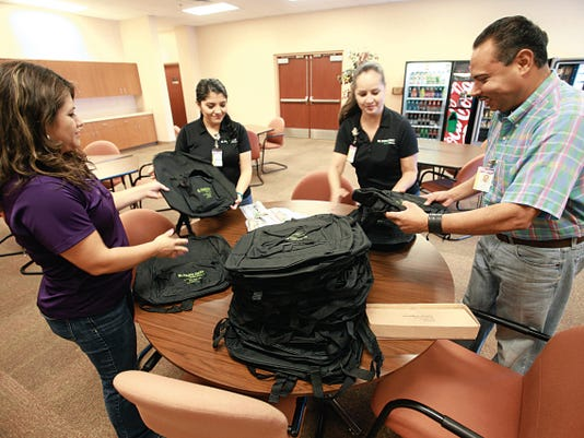 El Paso First Health Plans employees, from left, Adriana Cadena, Lluvia Acuna, Suzana Ciriza and Jesse Salomon gather backpacks that the group will be giving to 500 students during a health fair today.