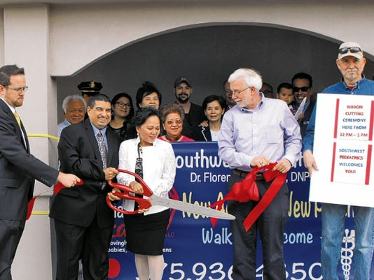 Members of the Deming-Luna County Chamber of Commerce help Dr. Florence Roque and her husband, Joel, cut the ceremonial ribbon at their new business Southwest Pediatric Care at 1020 S. Eighth St.
