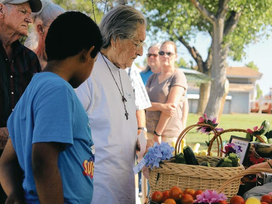 A woman with a Farmers Market Nutrition Program voucher examines fresh produce at the Grown on Faith stall at the Alameda Park Farmers Market in Alamogordo.