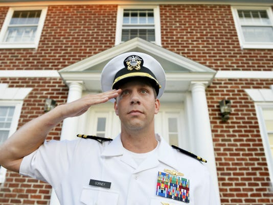 "Joshua Corney stands for a portrait outside his Glen Rock home on Saturday, July 25, 2015. Corney, a lieutenant, is serving his 18th year in the U.S. Naval and recently moved his family to Glen Rock, where he grew up. Corney plays a recording of ""Taps"" outside his home every evening at 8 p.m. in remembrance of military service members, and plans to build a memorial for local veterans at the bottom of his driveway."