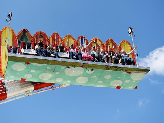 Fair-goers raise their arms on a ride during opening