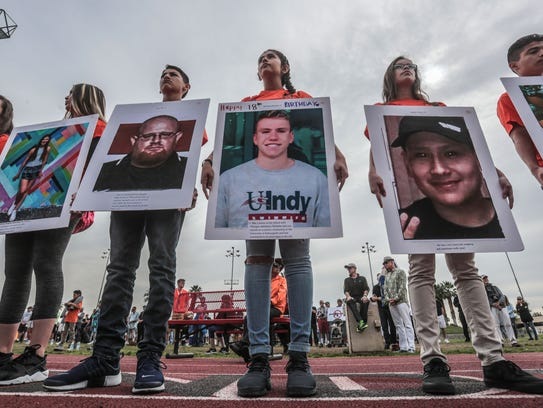 Students with pictures of those killed at Marjory Stoneman