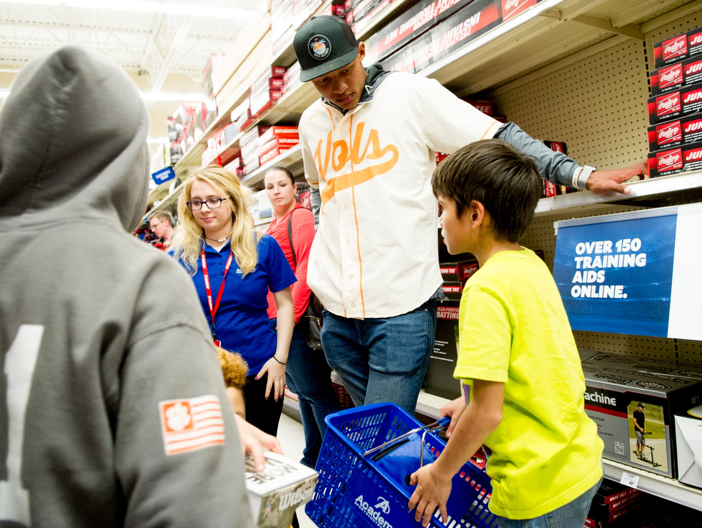 Former UT QB Joshua Dobbs helps kids pick football gear during a football sporting goods shopping spree at Academy Sports + Outdoors in Knoxville, Tennessee on Friday, March 31, 2017. Dobbs held a shopping spree for 11 area kids who are participating in his football camp.