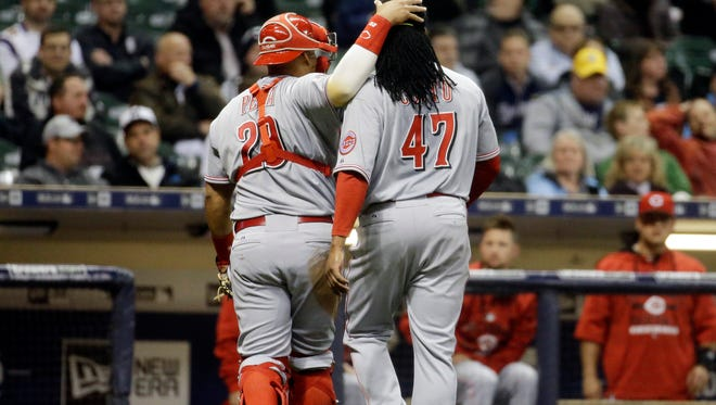 Reds catcher Brayan Pena (left) congratulates starting pitcher Johnny Cueto after the Brewers' Adam Lind struck out to end the eighth inning Wednesday night in Milwaukee.