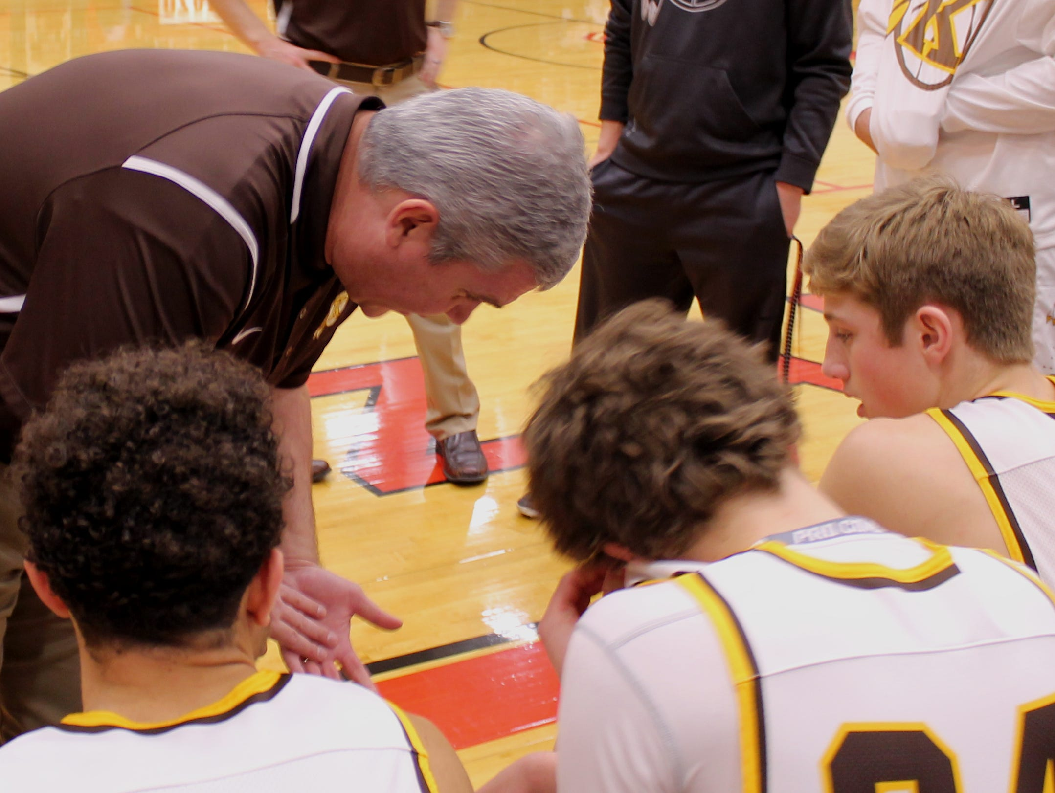 Kickapoo boys basketball coach Dick Rippee leans down to be heard over the stereo system at Ozark High School as he instructs starters, from left, Isaac Johnson, Jared Ridder and Travis Vokolek prior to a game against Barstow in the Scoreboard Guy Shootout.