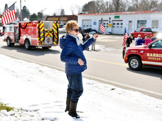 Jan Mooney of Stewartstown holds an American flag as the funeral procession of Lt. Dennis DeVoe passes Saturday, March 18, 2017. Following a hometown funeral service at Grace Fellowship Church in Shrewsbury, a procession led by a fire engine bearing DeVoe's coffin traveled from Shrewsbury through Stewartstown to Fawn Grove. Career firefighter DeVoe, 45, was killed in the line of duty March 10 when a suspected drunken driver struck his vehicle as he was responding to a fire in Harrisburg. DeVoe was a 21-year veteran of Harrisburg Bureau of Fire and had at one time volunteered with Eureka Volunteer Fire Company in Stewartstown, among others.