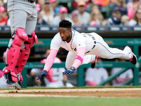 Niko Goodrum of the Detroit Tigers dives into home