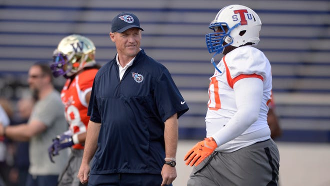North squad head coach Ken Whisenhunt of the Tennessee Titans walks amongst players during Senior Bowl North squad practice at Ladd-Peebles Stadium on Tuesday.