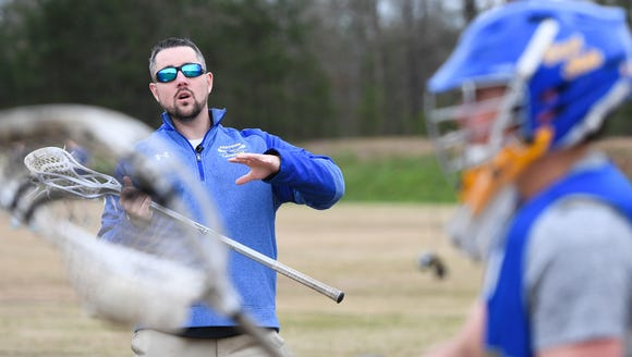 Eastside lacrosse coach Mike McCallan works with goalie Jamison Lowry during the team's practice on Monday, March 26, 2018. McCallan is back coaching after having brain surgery to remove a benign tumor behind his optic nerve.