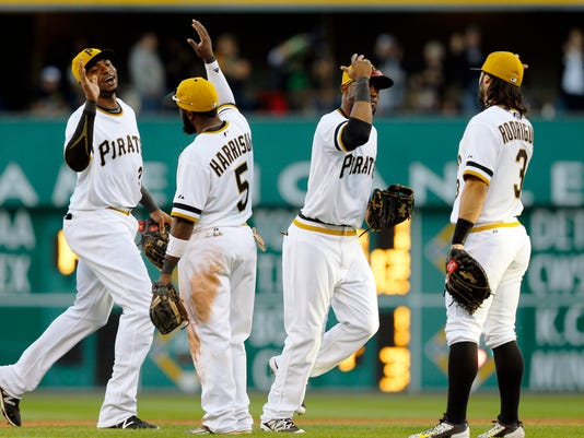 Pittsburgh Pirates outfielders Gregory Polanco, left, and Starling Marte, center right, celebrate with infielder Josh Harrison (5) and Sean Rodriguez (3) after defeating the Cincinnati Reds in a baseball game, Sunday, Oct. 4, 2015, in Pittsburgh. The Pirates won 4-0 and clenched the home field for their upcoming wild-card playoff game against the Chicago Cubs. (AP Photo/Keith Srakocic)