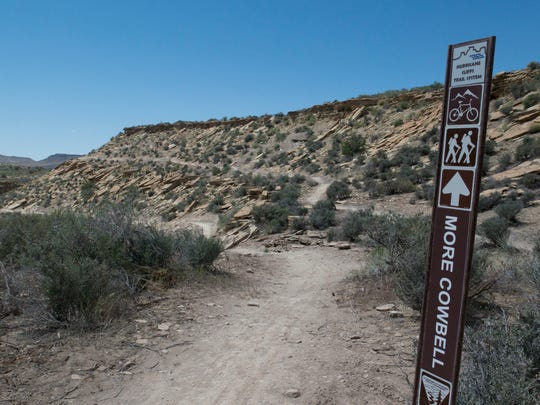 A sign points the way to More Cowbell as it diverges away from the Dead Ringer Trail in the Hurricane Cliffs Trail System Wednesday, April 15, 2015.