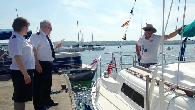Salvation Army officers Tricia and Jim Brennan, left, bless a boat owned by John Murphy, right, at the Canandaigua Yacht Club Saturday.