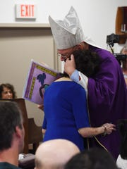 Cardinal Timothy Dolan gives a hug to resident Kathleen Hart during mass at ArchCare at Ferncliff Nursing Home and Rehabilitation Center in Rhinebeck. The residents made Cardinal Dolan a card for Easter.