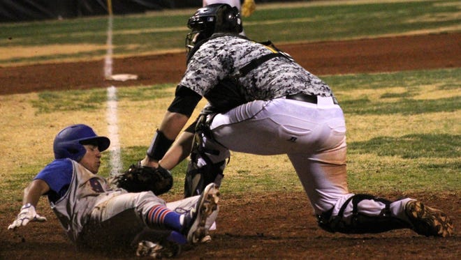 Las Cruces' Ivan Molina slides underneath the tag by Alamogordo's Thompson Rick on Friday night at Tiger Field.