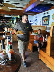 Mike Dangerfield, a manager at Zogg's Raw Bar and Grill in Rehoboth Beach, serves a customer Wednesday.