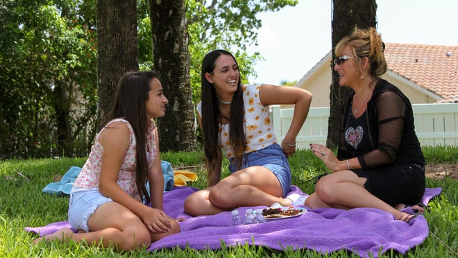 "Jazz Jennings, left, at the park with her sister, Ari, and their mother, Jeanette, in a scene from ""I Am Jazz."""