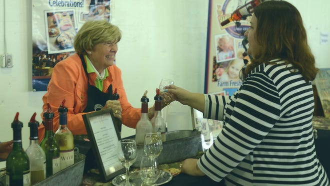 Gene Pilarski, left, hands a wine glass over to Cheryl Parlove during a Thumbs Up Wine Trail event on Sunday, May 21, 2017, at the Port Huron Seaway Terminal. Both said they were volunteers with the Optimists in Shelby Township, one of the several charities to benefit from the event.