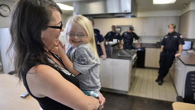 Sophina Lindquist, 6, giggles with her mother, Connie, as they visit the St. Cloud Fire Department's Station 1 on Sunday. Sophina Lindquist, who has Down syndrome, regularly visits with, and prays for, the firefighters with her mom and siblings as a way to say thank you for the service they provide.