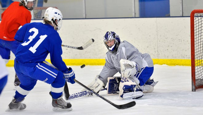 Sartell goalie Matthew Partch stops a shot from teammate Keenan Lund (31) during a practice drill Monday at Bernick's Arena.