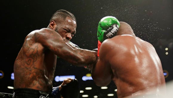 Deontay Wilder, left, punches Luis Ortiz during the