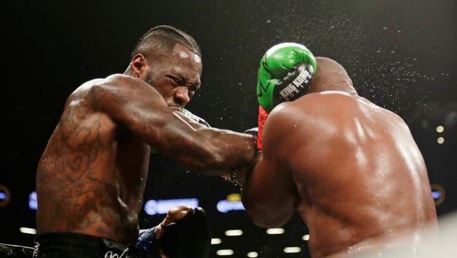 Deontay Wilder, left, punches Luis Ortiz during the fifth round of the WBC heavyweight championship bout Saturday, March 3, 2018, in New York. Wilder won in the 10th round. (AP Photo/Frank Franklin II)