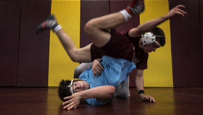 Riverdale High School wrestler Nelson Ortiz works out with a teammate during an after school practice Monday, January 23.