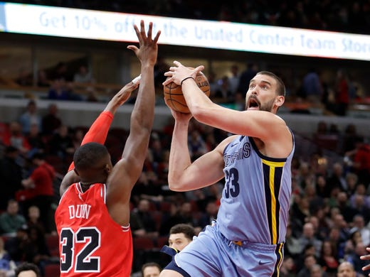 Memphis Grizzlies' Marc Gasol, right,  drives to the basket as Chicago Bulls' Kris Dunn, left, defends during the first half of an NBA basketball game Wednesday, March 7, 2018, in Chicago. (AP Photo/Charles Rex Arbogast)