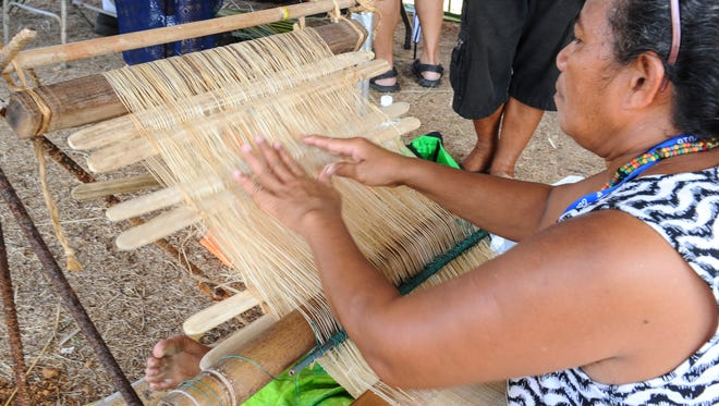 Festival goers watch as Solomon Islands delegate member Catherine Noholia weave fibers from a hibiscus plant into panels of material on a traditional loom during the Festival of Pacific Arts at the Sagan Kotturan Chamoru cultural center in Tumon on Monday, May 30. Noholia says she started weaving 11 years ago after learning from her grandmother in the Sikaiana Atoll of the Solomon Islands.