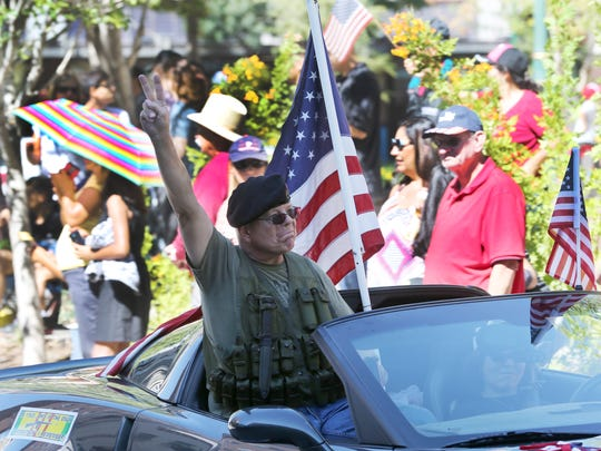 """A Vietnam veteran flashed a """"V"""" sign as he rode in a car during Sunday's Welcome Home Vietnam Veterans Parade in Downtown El Paso Sunday."""