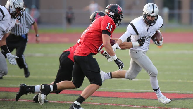 Livonia Churchill's Steven Szymanski (front) closes in on Plymouth running back Cameron Stella during Friday's game.