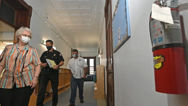City officials conduct a fire safety inspection of St. Benedict Center, 345 E. Ninth St., on Tuesday. From left are Benedictine Sister Diane Rabe, the center's director; Darren Hart, chief fire inspector for the Erie Bureau of Fire; and Scott Heitzenrater, building inspector for the city of Erie.