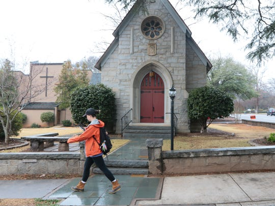 A Clemson University student walks by the oldest building on the property of Saint Andrew Catholic Church in Clemson.